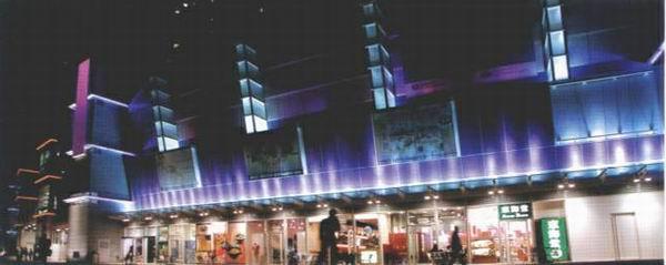 奥海城是位于九龙大角咀的一个商场及住宅区,所处位置是一个新区,业主希望用灯光来吸引人们的注意。关永权特意用不同的方法在外墙做出七彩的灯光效果,以多种颜色构成一个眩目无限、五彩缤纷的新商场形象。  项目分四期,第一期是四个塔楼。关永权有不同的霓虹灯加400W的泛光灯,灯光在四个塔楼间有节奏地变化着,四种不同色彩的灯似四个不同的图案来回不断地变色,在晚上显得特别耀目。  在这里,用霓虹灯和泛光灯,配上控制系统,构成动感十足的气氛。    第二期的商场外墙有几个不同的面,关永权将灯藏在玻璃幕墙之间;另外有像满天